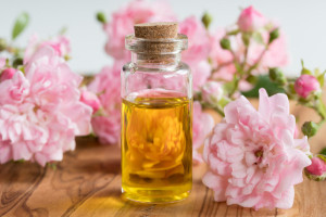 A bottle of rose essential oil with small rose blossoms on a wooden background